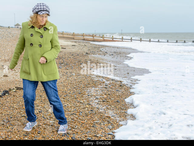 Middle aged woman dodging waves on a beach by the sea. - Stock Image