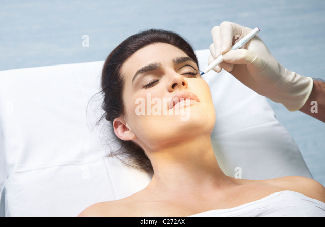 Doctor's Hand Marking Woman's Eyelid with Pen - Stock Image