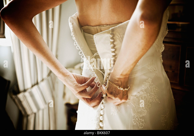 A Woman Buttoning Up The Back Of Her White Wedding Dress - Stock Image