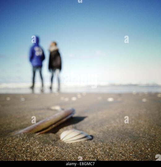 Two children walking along beach - Stock Image