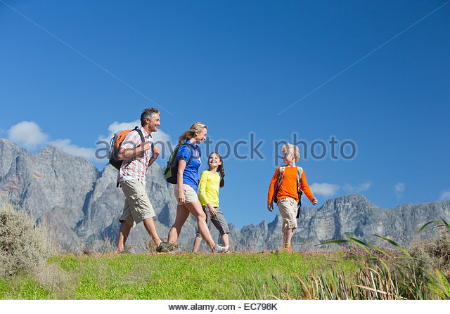 Family hiking on a mountain path - Stock-Bilder