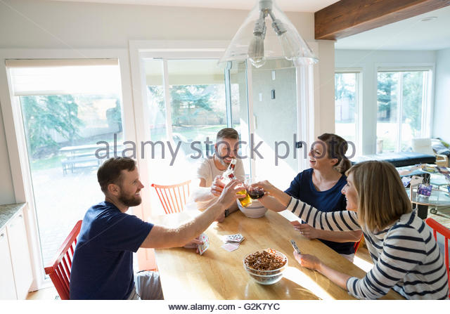 Couples toasting beer and playing cards at dining table - Stock Image
