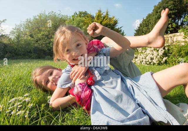 Girls playing together in grassy field - Stock-Bilder