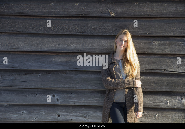 A young woman leaning against the wooden wall of a barn wearing a long knitted coat. - Stock Image