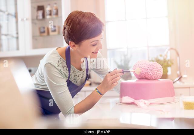 Female caterer finishing pink wedding cake in kitchen - Stock-Bilder