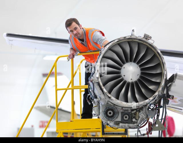 Engineer inspecting jet engine - Stock Image
