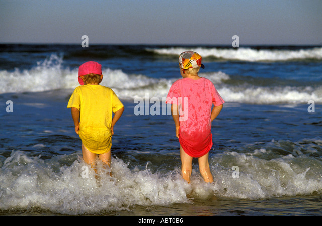BEACHES Boys Colorfully Dressed Standing in Surf - Stock Image