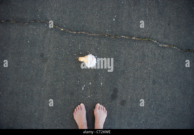 A person's feet with dropped ice cream cone on pavement. - Stock Image