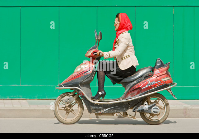 A Chinese woman travels along a road on her scooter in Kashgar. - Stock Image