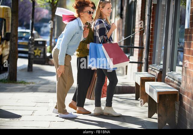Side view of women holding shopping bags standing in street looking in shop window - Stock-Bilder