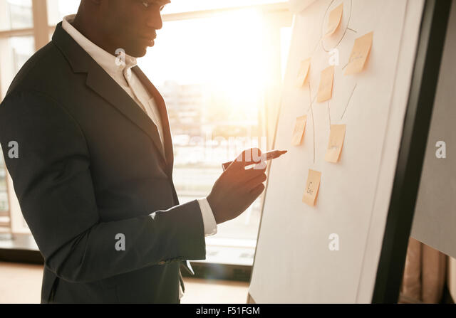 Cropped shot of businessman presenting his ideas on white board. Business executive with marker pen writing in flipchart - Stock Image
