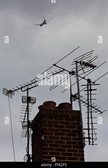 An aeroplane flying high over TV aerials on a roof in the village of Hatton near London Heathrow. - Stock Image