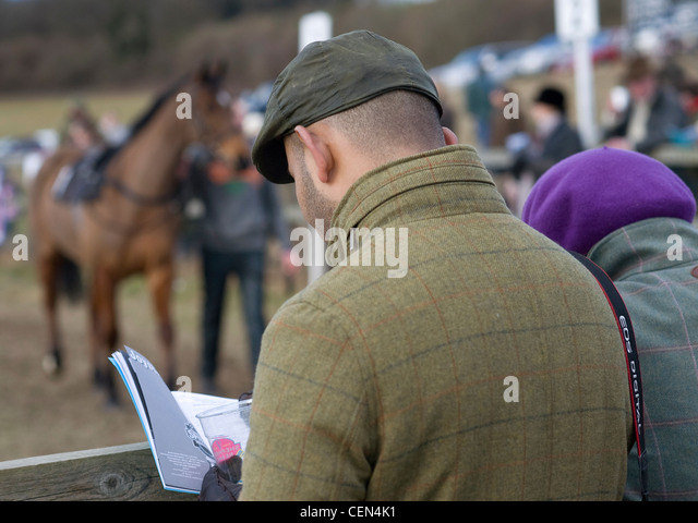 A punter reads the race card before the Shepherd Neame Mens Open Race at the South East Hunts Club Point to Point - Stock Image