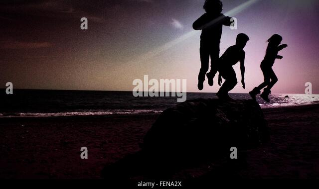 Silhouette Children Jumping At Beach During Sunset - Stock Image