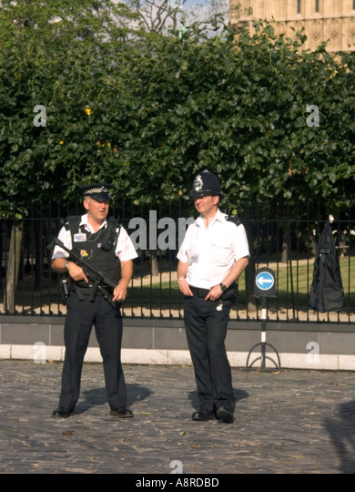 Armed Police officers guard the Houses of Parliament London England - Stock Image