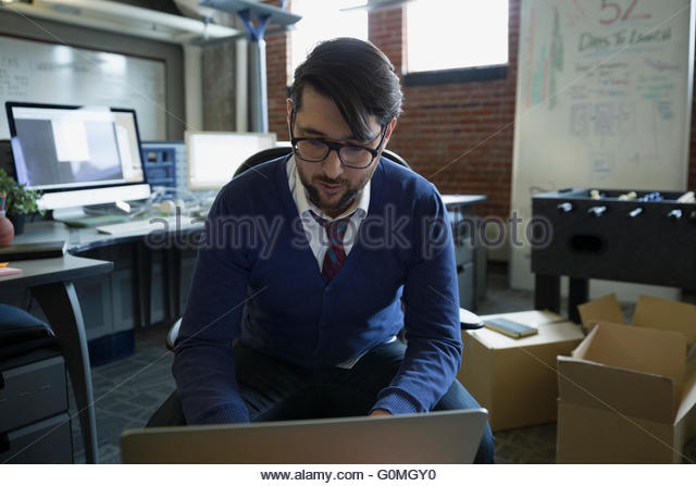 Entrepreneur using laptop in new office - Stock-Bilder