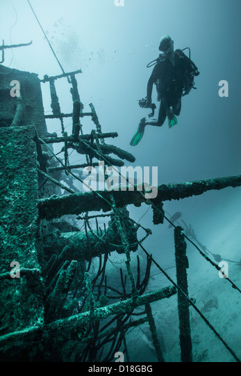Diver examining underwater shipwreck - Stock Image