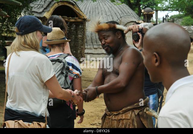 View of Zulu man in traditional dress greeting tourists at theme village Shakaland KwaZulu-Natal South Africa Cultures - Stock-Bilder