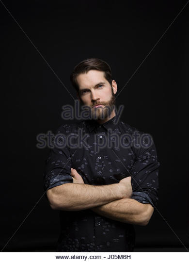 Portrait serious tough brunette man with beard and arms crossed against black background - Stock Image