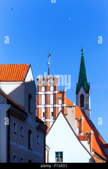 Latvia. Riga. The facade of the old house and the green spire of the ancient church on a cockerel weather vane in - Stock Image