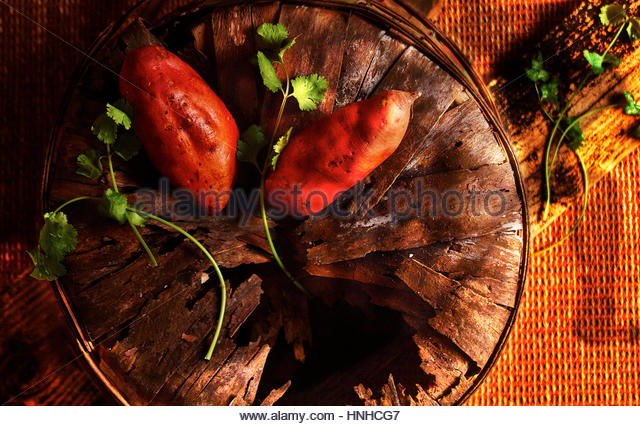 Tow sweet potatoes in a barn setting - Stock Image