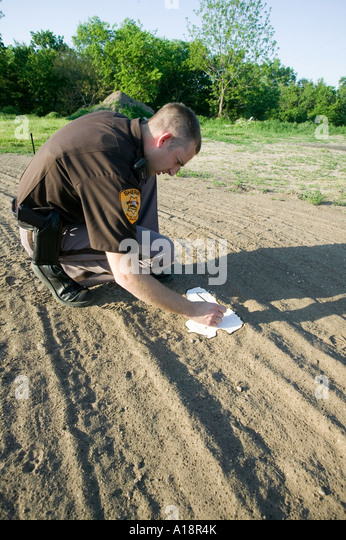 Deputy sheriff writing the date on a plaster cast of a shoe print prior to the plaster drying - Stock Image