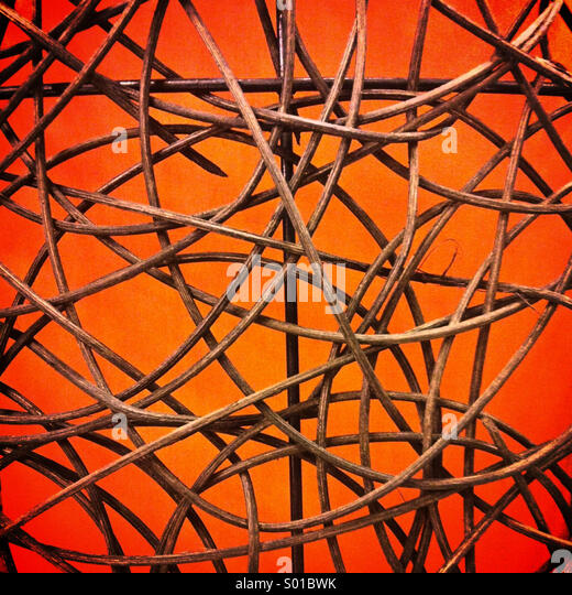 An abstract pattern of bent wooden sticks against a lighted orange glowing background - Stock-Bilder