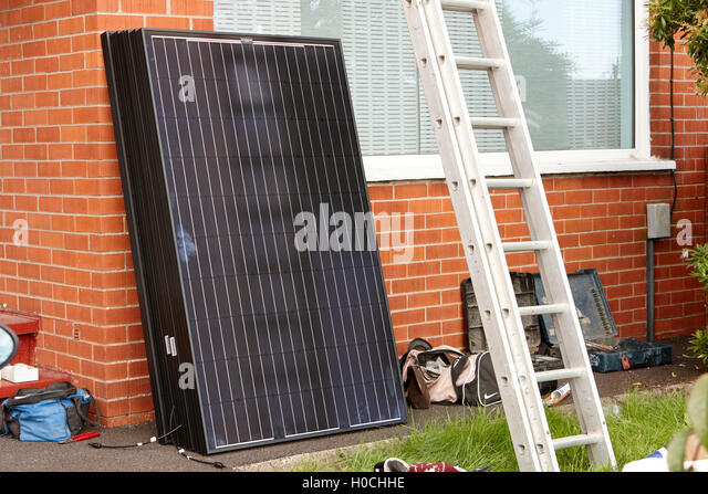 black solar panels for installation in a domestic solar panel installation in the uk - Stock Image