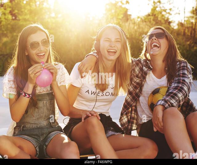 Group of girls laughing while sitting outside enjoying the summer - Stock-Bilder