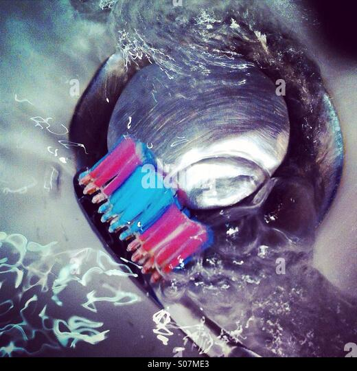 Cleaning the toothbrush with water near the sinkhole - Stock Image