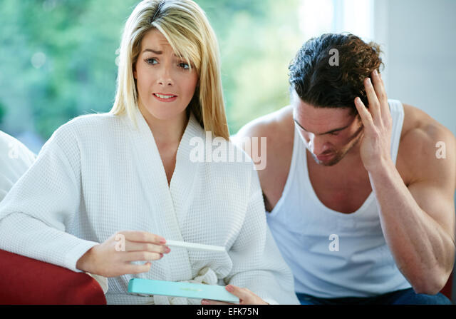 Unhappy couple finding out she is pregnant - Stock Image