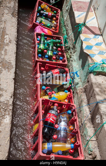 Cooling soft drinks in a water channel - Stock Image