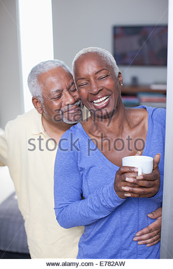 Smiling older couple hugging indoors - Stock Image