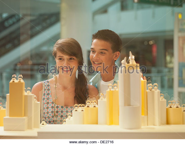 Smiling couple looking at jewelry in display case - Stock Image