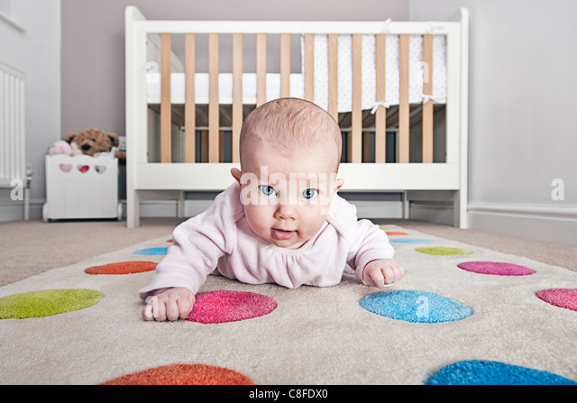 Babys First Crawling Attempts in Nursery - Stock Image