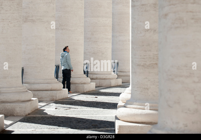 Man walk in colonnade in St Peter's Square. - Stock Image