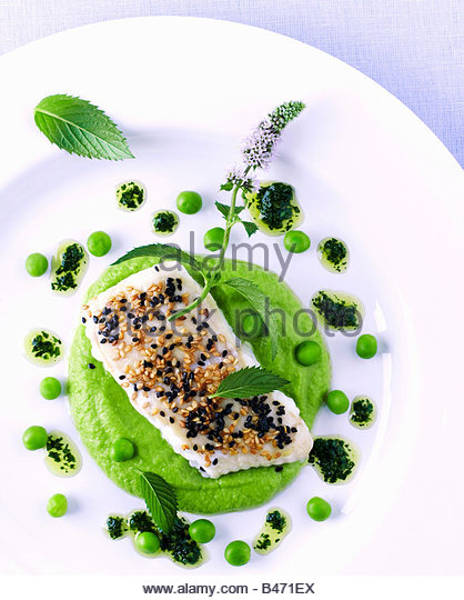 Fish fillet with sesame on pea puree and lime vinaigrette - Stock Image