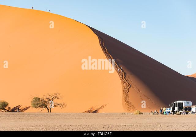 Tourists climbing sand dunes, Sossusvlei, Namib Desert, Namib-Naukluft Park, Hardap Region, Republic of Namibia - Stock Image