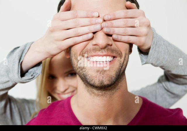 Woman covering eyes of man, smiling, close up - Stock Image