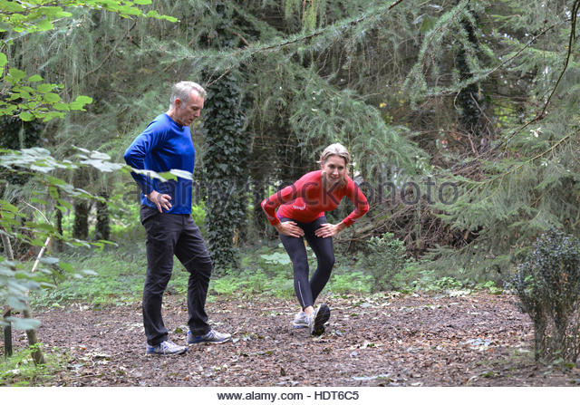 Mature married couple stretching in forest. - Stock Image