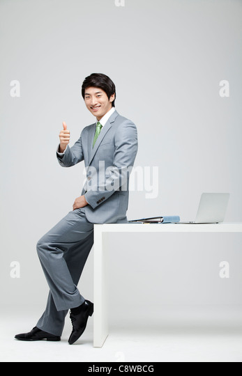 Portrait Of Businessman Showing Thumb Up Sign, Laptop And File On Desk - Stock Image