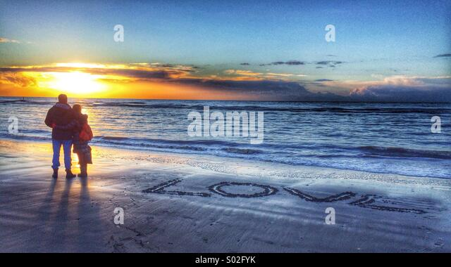 A couple stand at the shore watching the sunset the word Love inscribed into the sand next to them - Stock Image