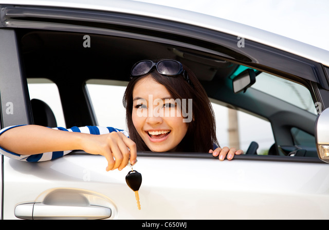 young happy woman in car showing the keys - Stock Image