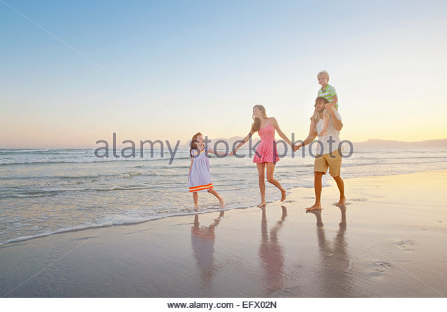 Happy family walking, holding hands and son having piggy-back, on sunny beach - Stock Image