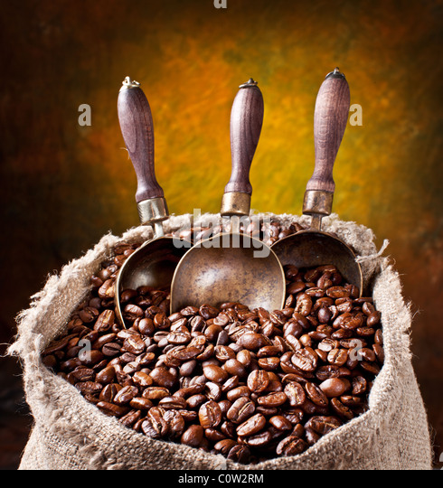 Sack of coffee beans and scoop. On a dark background. - Stock Image