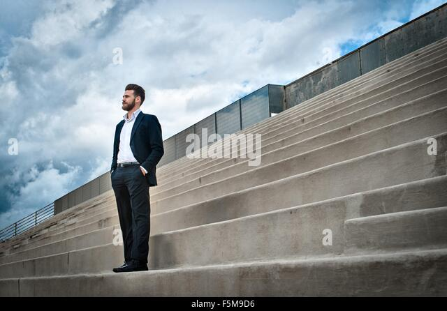 Low angle view of mid adult man on steps wearing suit, hands in pockets looking away - Stock-Bilder