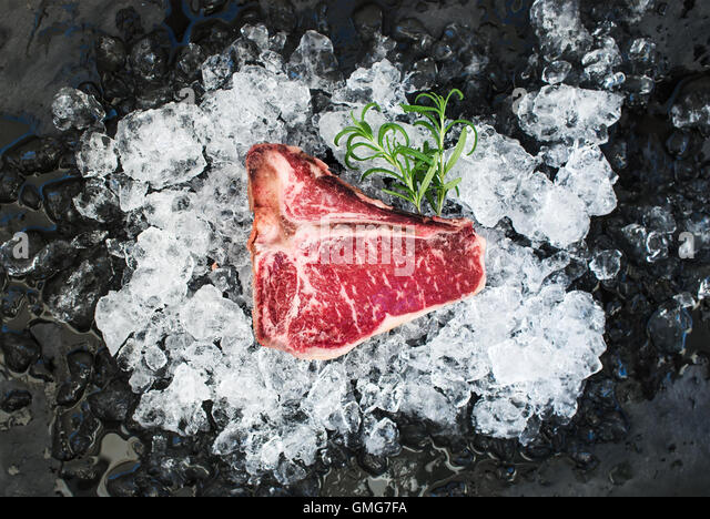 Raw fresh meat t-bone steak on chipped ice with rosemary - Stock Image
