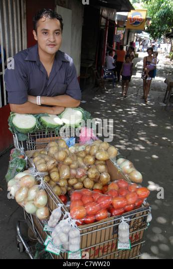 Managua Nicaragua Mercado Roberto Huembes market shopping shopping produce street vendor cart bags cabbage tomatoes - Stock Image