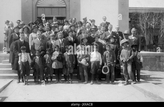 Full length landscape shot of adults and children all standing in rows, some African American, all dressed formally, - Stock Image