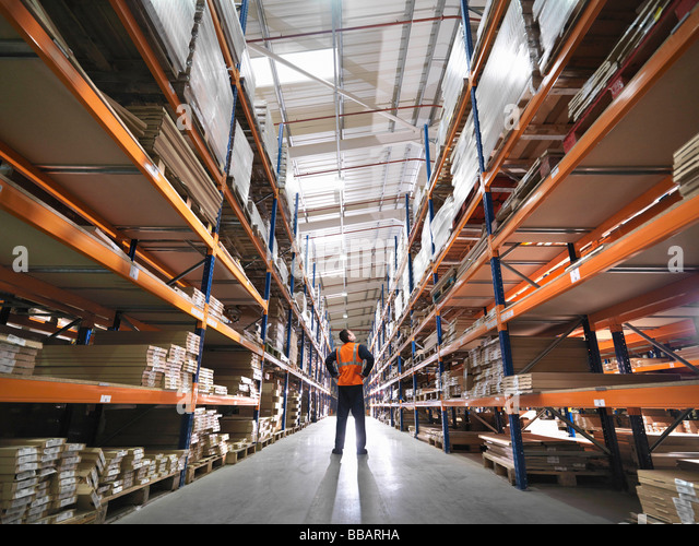 Worker Inspecting Goods In Warehouse - Stock Image